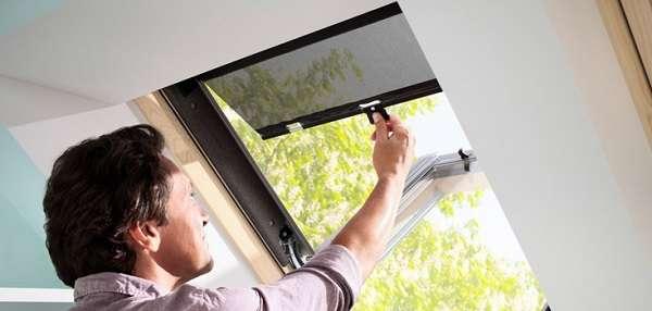 Monsieur qui protège sa fenêtre de toit du soleil