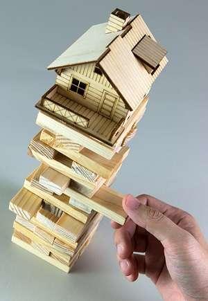 Fondation maison : une personne enlève une pièce d'un jeu de construction