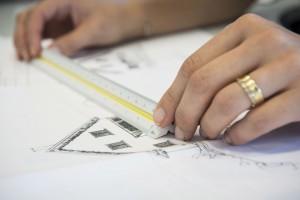 mains d'une femme sur un plan de maison papier en train de mesurer