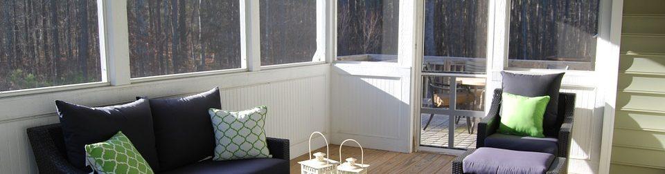 Salon de véranda avec canapé et coussins