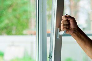 main d'homme qui ouvre la fenêtre oscillobattante