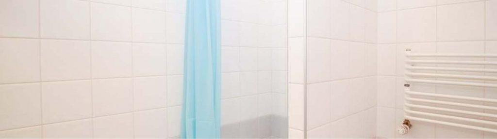 salle de bain avec rideau bleu clair et carrelage