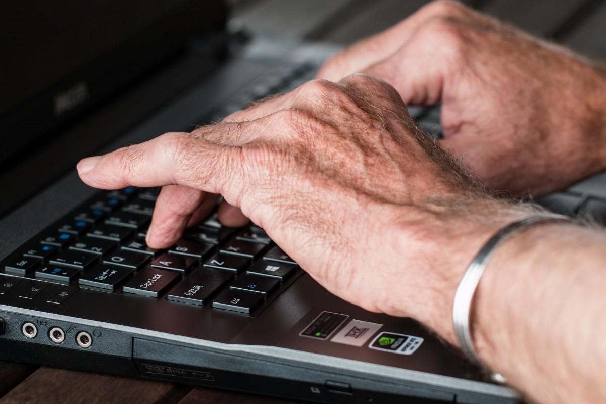mains de senior sur un clavier d'ordinateur