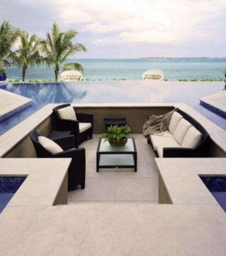 Petit salon en plein air, entouré d'une piscine et d'un superbe décor de palmiers