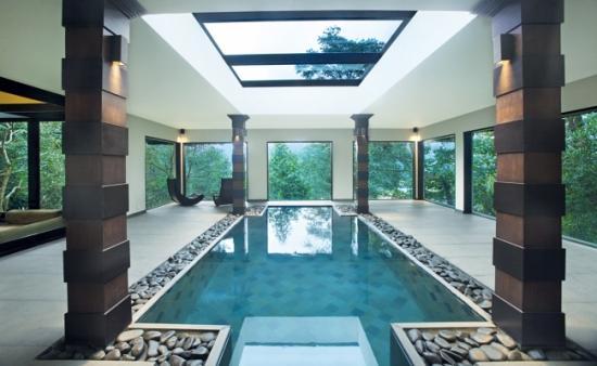 Piscine intérieure dans une sorte de grande véranda lumineuse avec des colonnes et des pierres autour de la piscine