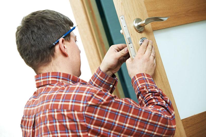 homme en chemise à carreaux qui règle une serrure de porte en bois